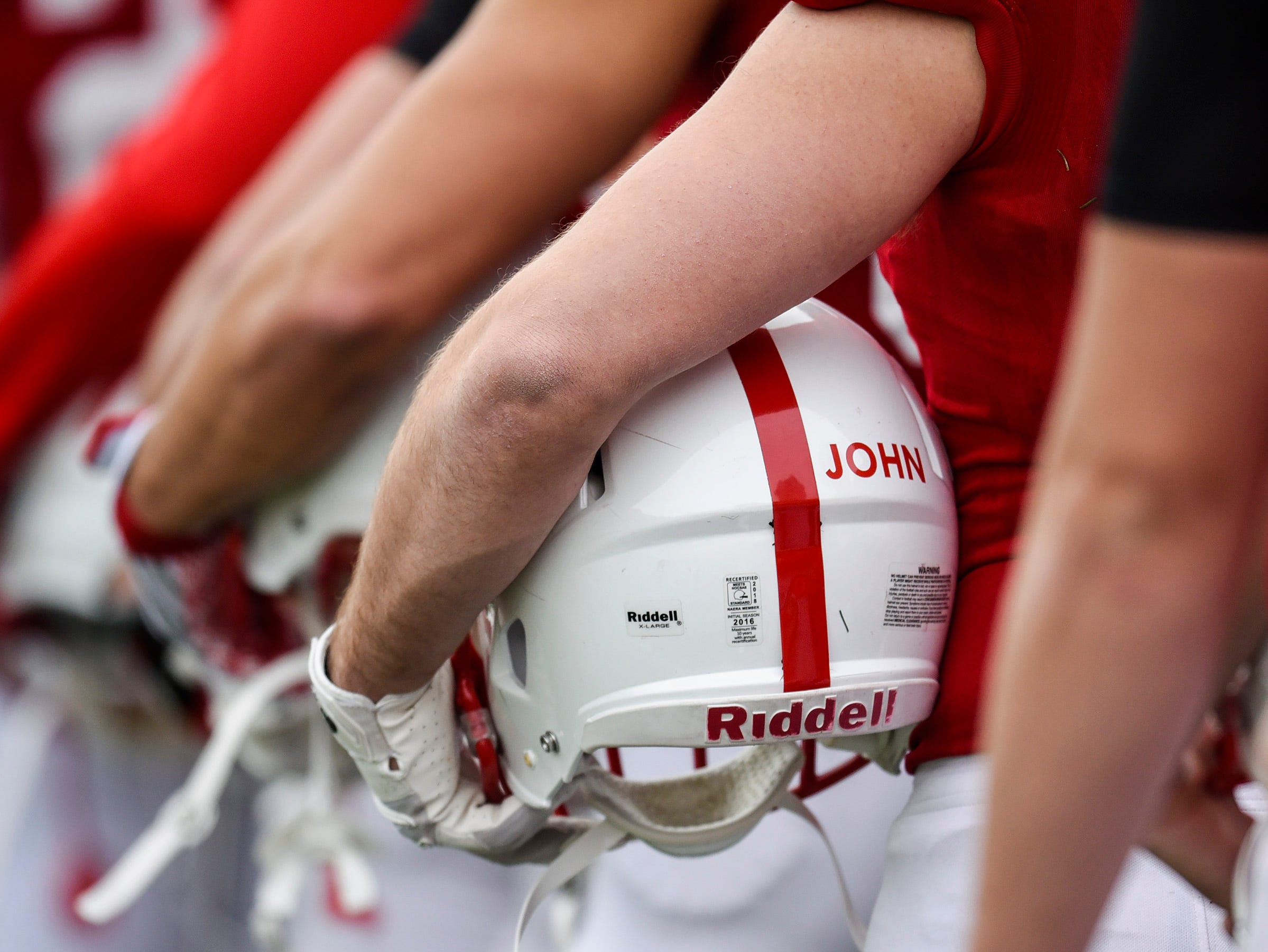 """St. John's football players remember coach John Gagliardi with """"John"""" on the back of their helmets Saturday, Oct. 13, in Collegeville."""