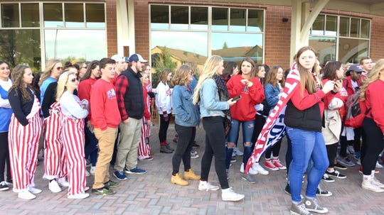 A group of Johnnies fans, mostly students at College of St. Benedict and St. John's University, line up in front of the Gorecki Center in St. Joseph while waiting to load a bus to Collegeville for the Johnnies/Tommies game Saturday, Oct. 13.
