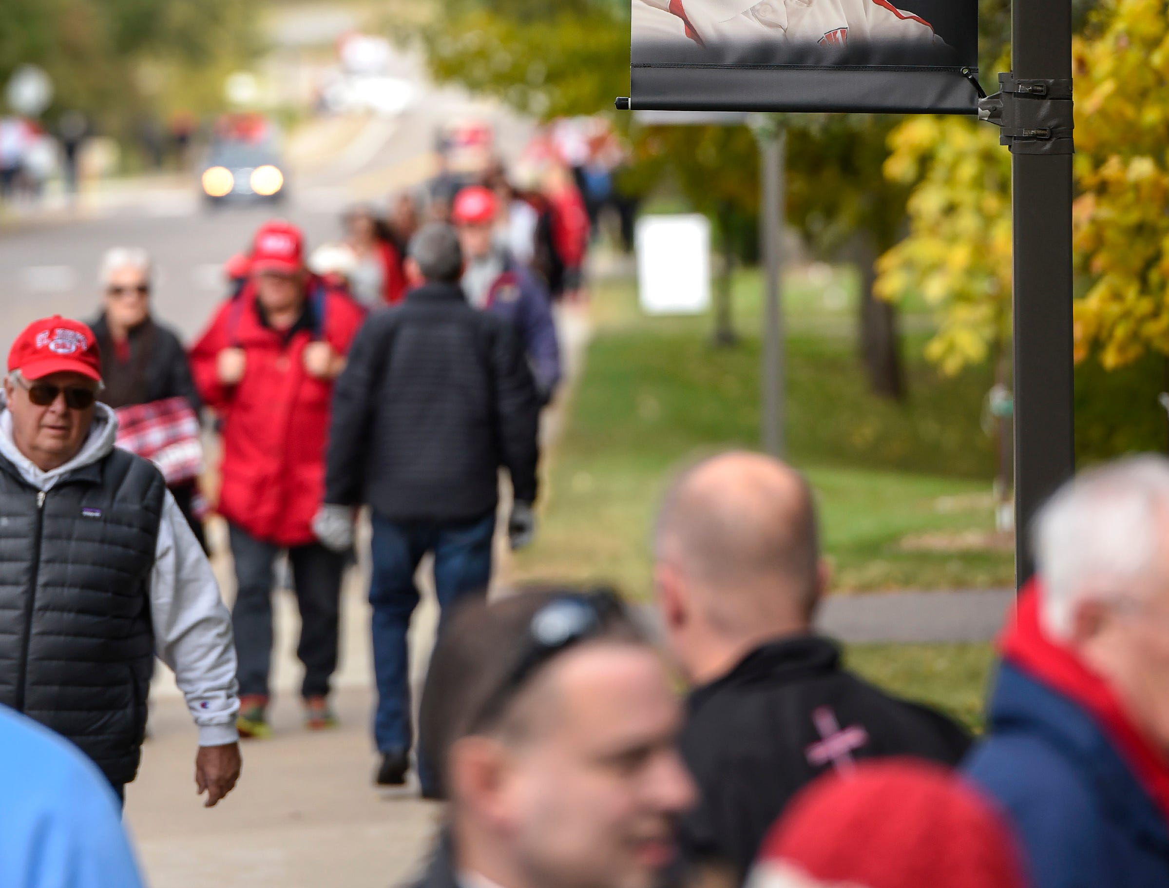 Banners in memory of John Gagliardi hang on light poles around Clemens Statium as fans enter the football game Saturday, Oct. 13, in Collegeville.