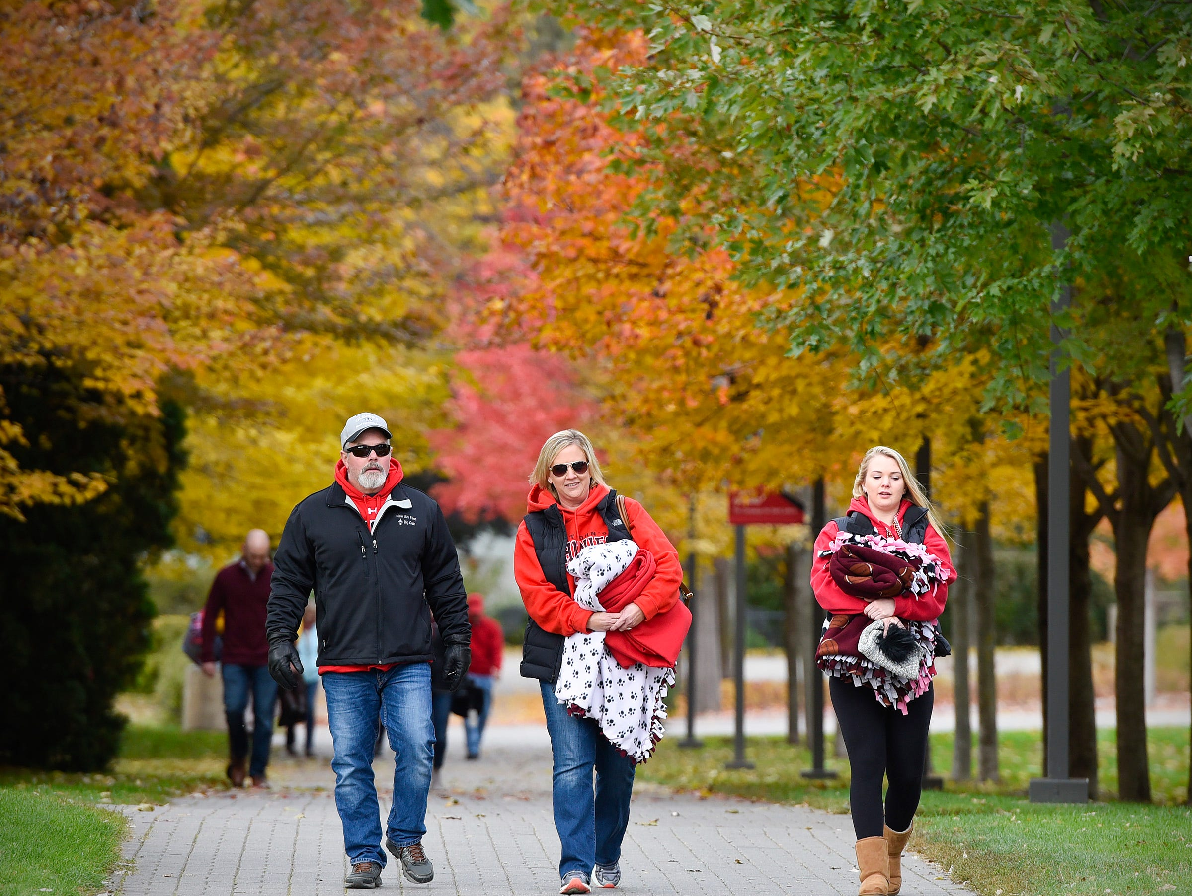 Fans walk through the colorful leaves on campus to get to the St. John's and St. Thomas game Saturday, Oct. 13, in Collegeville.