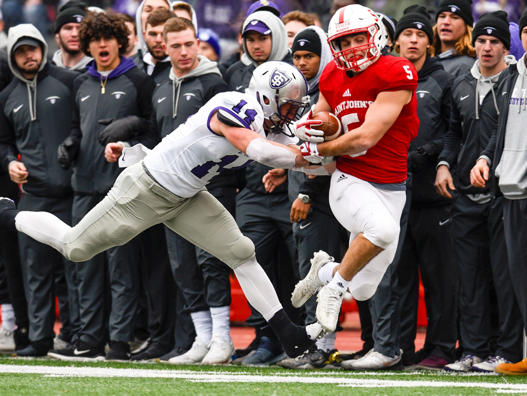 St. John's running back Adam Essler fights to stay in bounds on a run against St. Thomas during the first half Saturday, Oct. 13, in Collegeville.