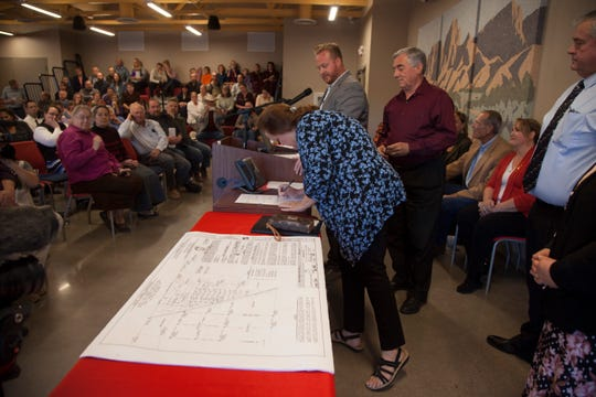 Colorado City residents and UEP Trust representatives look on as a newly deeded homeowner signs a document Friday, Oct. 12, 2018.