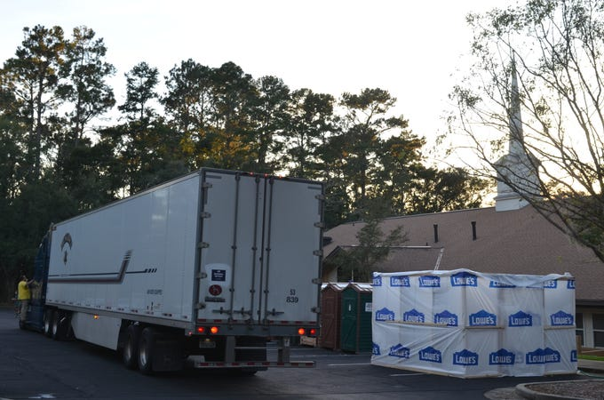 Volunteers unload a truck of supplies that would be used for the Mormon Helping Hands.