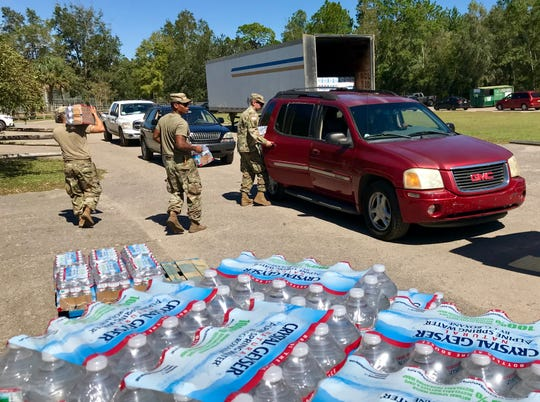 Florida National Guard troops from Lake Wales hand out water to a long line of vehicles.
