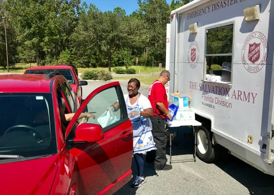 Debra Boswell, a Salvation Army volunteer from Tallahassee, hands out hot food to people Saturday at the Woodville branch library.