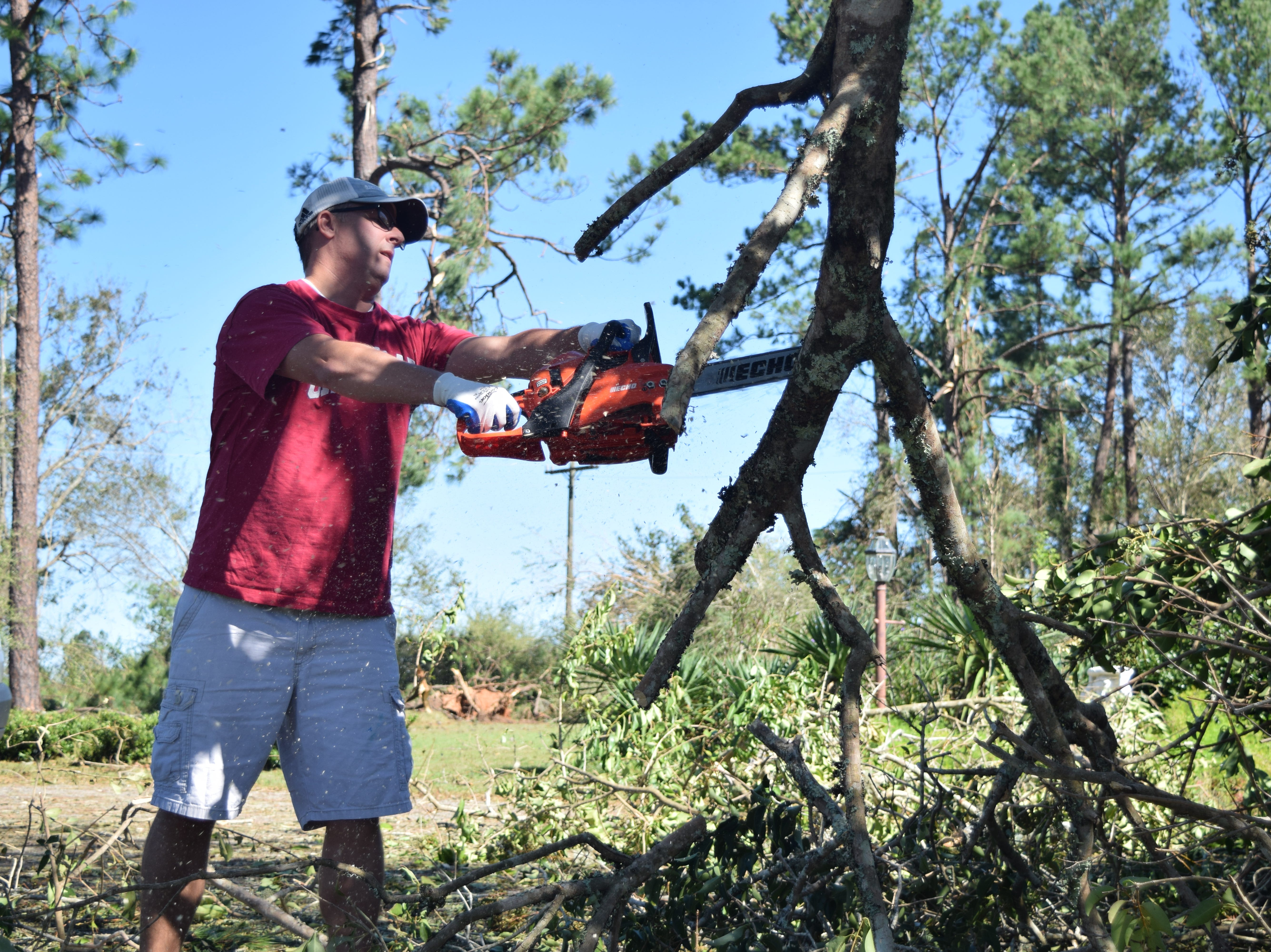 Trey Homan, a volunteer with Mormon Helping Hands, cuts up a tree at a house in Quincy after Hurricane Michael.