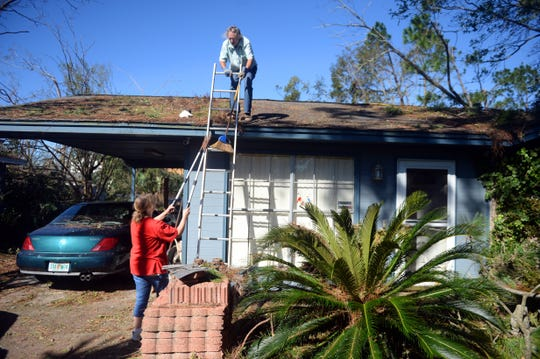 "Oct. 12, 2018, Panama City, FL, USA; Jeanette Mann passes a large tree trimmer to her husband, Wayne, as he clears debris from the roof their Panama City home left after Hurricane Michael blew through the area. ""We had some damage to the home but we made it through alright,"" Jeanette Mann said."