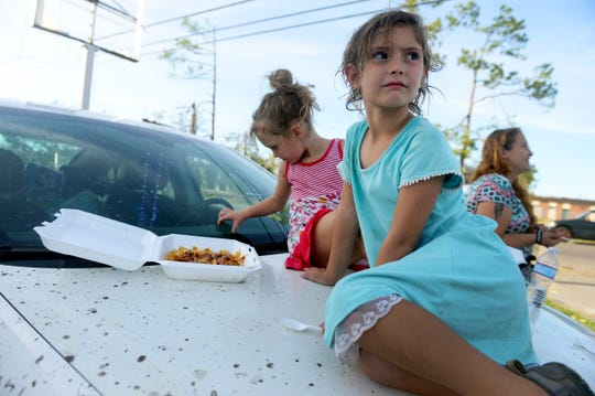 "Oct. 12, 2018, Panama City, FL, USA; Cesaleigh Aldridge, 7, sits with her sister Cydaleigh, 5, on the hood of her mother's car ready to eat dinner served by a Salvation Army food truck in Panama City on Friday, Oct. 12, 2018. After Hurricane Michael blew through the area on Wednesday, residents were left without power, running water and many without food. ""We've been all over looking for something to eat,"" said the girls' mother Becca Aldridge. The Bay County school district will be closed for an undermined amount of time and Aldridge is considering trying to enroll her daughters in an Alabama school."