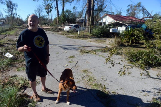 "Oct. 12, 2018, Panama City, FL, USA; Jeff Wurst walks his 8-month-old dog, Charlie, down his street littered with downed power lines and trees caused by Hurricane Michael. ""We spent the night in a shelter at Rutherford High School to ride out the storm,"" Wurst said. ""My wife has several medical problems so we are going to leave and get somewhere there is power and water until everything gets turned back on."""