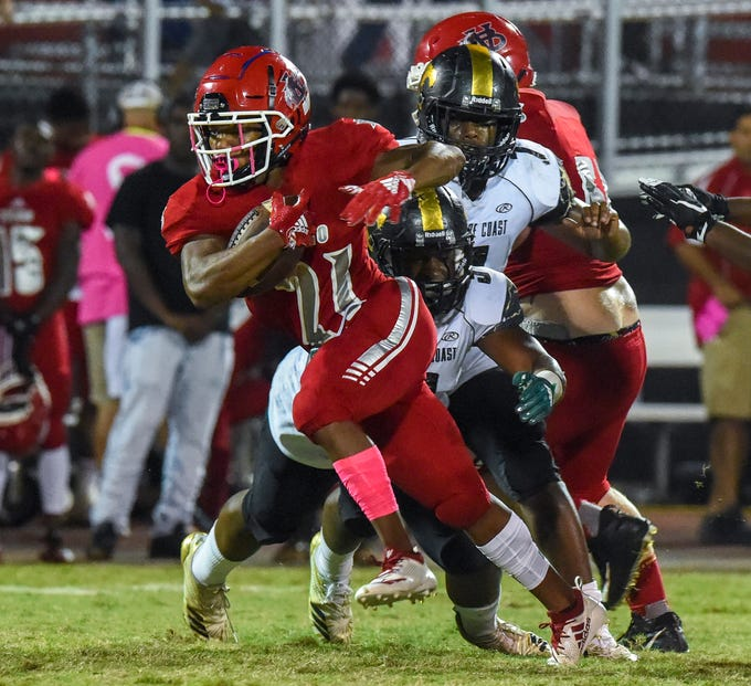 Vero Beach's Bryan Primus-Winston (21) gets past Treasure Coast defenders for positive yards Friday, Oct. 12, 2018, during their high school football game at Vero Beach High School. Vero Beach defeated Treasure Coast 34-31.