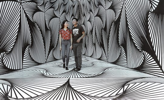 Erik Gonzalez and Jasmine Gaona tour an art installation by Laura Turon on Saturday at Chalk the Block in Downtown El Paso.