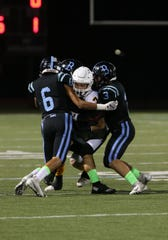 Ventura High quarterback Bryce Weinell gets sandwiched by Buena High's Christian Ayala, Amos Lira and Tyler Tonoli during Friday night's game. The Cougars won, 20-17.
