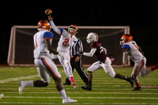 Millville quarterback Eddie Jamison Jr throws a long touchdown pass to Millville's Cartier Gray during Friday night's football game between Millville and Bridgeton, played at Bridgeton High School on October 12, 2018.