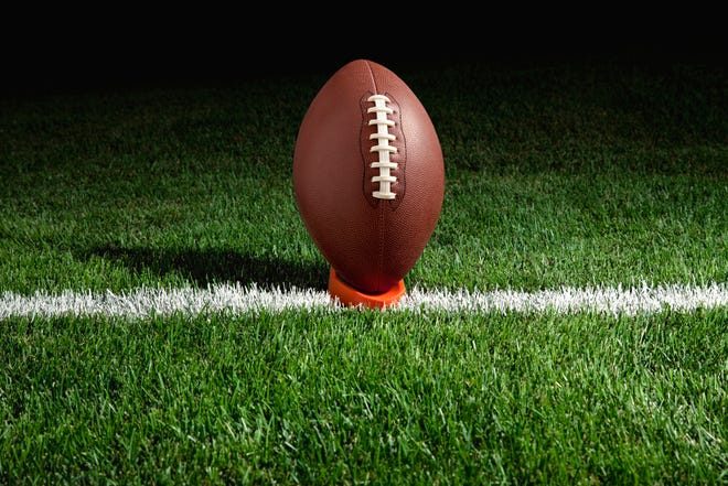 Football on tee at night