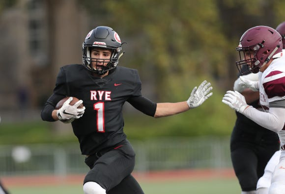 Rye's Matthew Tepedino (1) with the darry during their 34-28 win over Harrison in football action at Rye High School on Saturday, October 13, 2018.