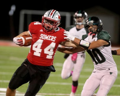 Jack Kaiser of Somers fends off Nick Campanaro of Yorktown as he rushes during a Class A playoff qualifying round game at Somers High School Oct. 12, 2018.