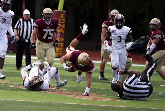 Iona Prep's Sean Fleming is tripped up by a Christ the King defender during a game on October 13th, 2018 at Iona Prep. Iona Prep would win the game 42-12.