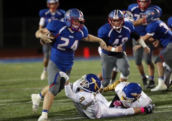 Carmel's Sam Duke tries to break away from Mahopac's Drew Riolo (8) looks for some running room in the Mahopac defense during football action at Carmel High School Oct. 11, 2018.