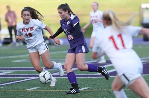 John Jay's Kaitlen Weis (25) moves the ball away from Rye's Leah Kenny (18) during girls soccer game at John Jay High School in Cross River on Oct. 13, 2018.