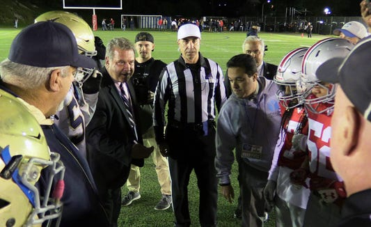 Yonkers Mayor Mike Spano, left, prepares to toss the coin before the inaugural football game between the Yonkers Brave and the Yonkers Force, at Saunders High School, Oct. 12, 2018.