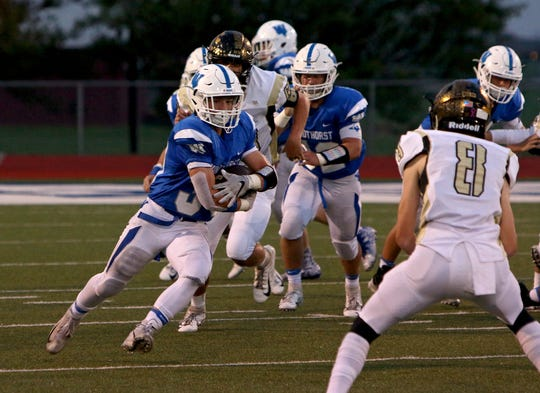 Windthorst's Ethan Belcher (39) looks to run past Archer City defender Conner Byrd (8) on Friday, Oct. 12, 2018, in Windthorst.