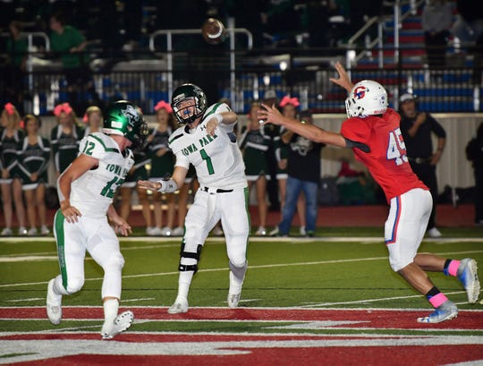 Iowa Park quarterback Trent Green (1) tosses a short pass out to Reid Lalk (12) as Graham's Landon Herbert (45) applies pressure Friday night at Newton Field in Graham.
