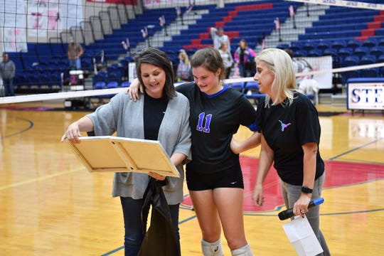 Meredith Sanders and her daughter, Sarah Sanders, receive an inspirational message from Shanna Iles during a presentation remembering the late David Sanders.