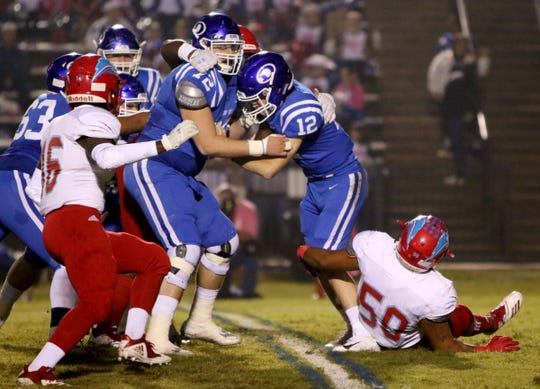 Decatur's Roman Fuller is sacked by Hirschi's Christian Hendricks and other Husky defenders Friday, Oct. 12, 2018, at Eagle Stadium in Decatur. The Eagles defeated the Huskies in a 22-21 upset.