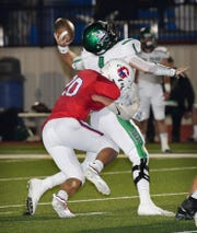 Iowa Park quarterback Trent Green is hit hard by Graham linebacker Raider Horn (20) causing Green to throw an interception during the second quarter of the game Friday night at Newton Field in Graham.