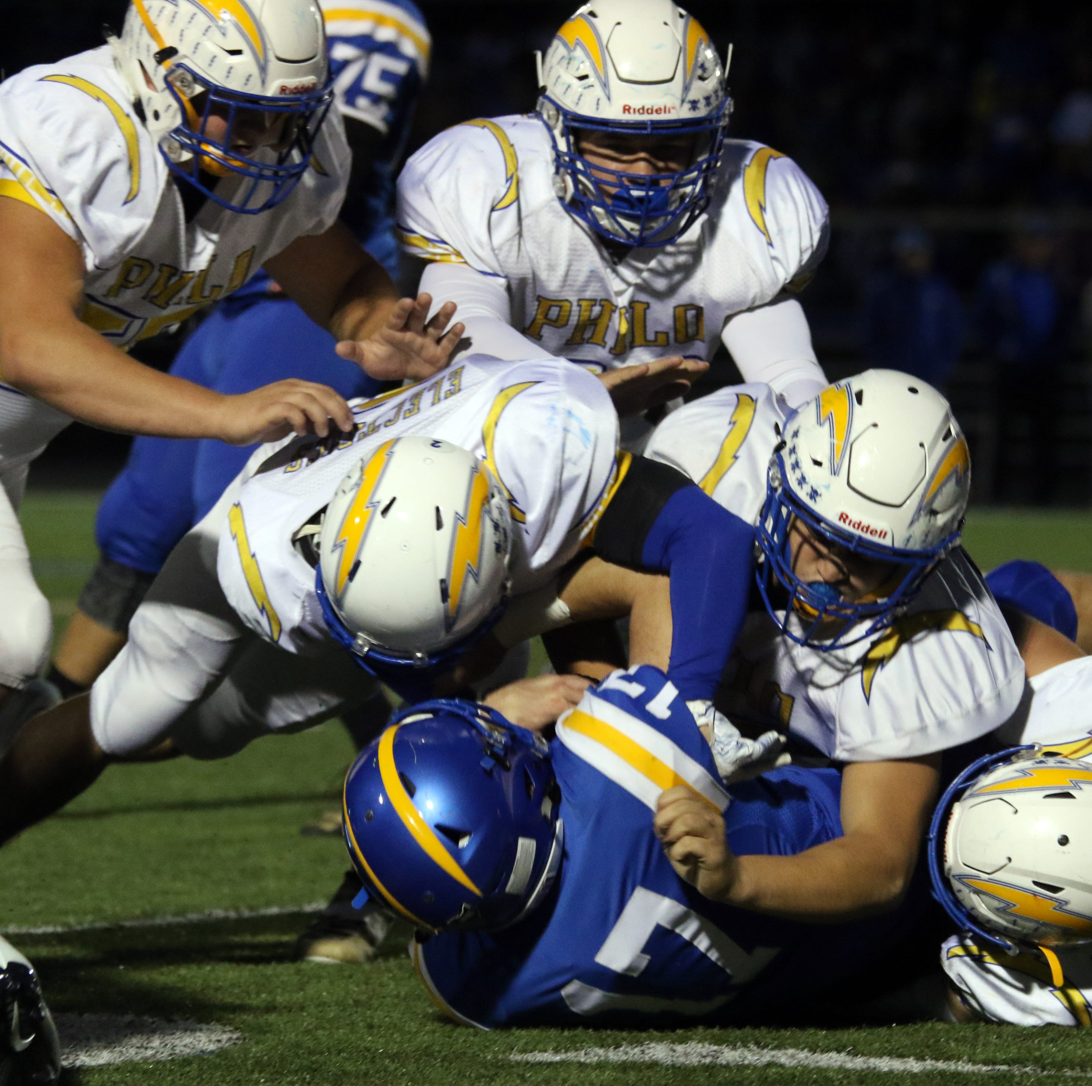 A host of Philo defenders tackle Maysville's Cle Tompkins.