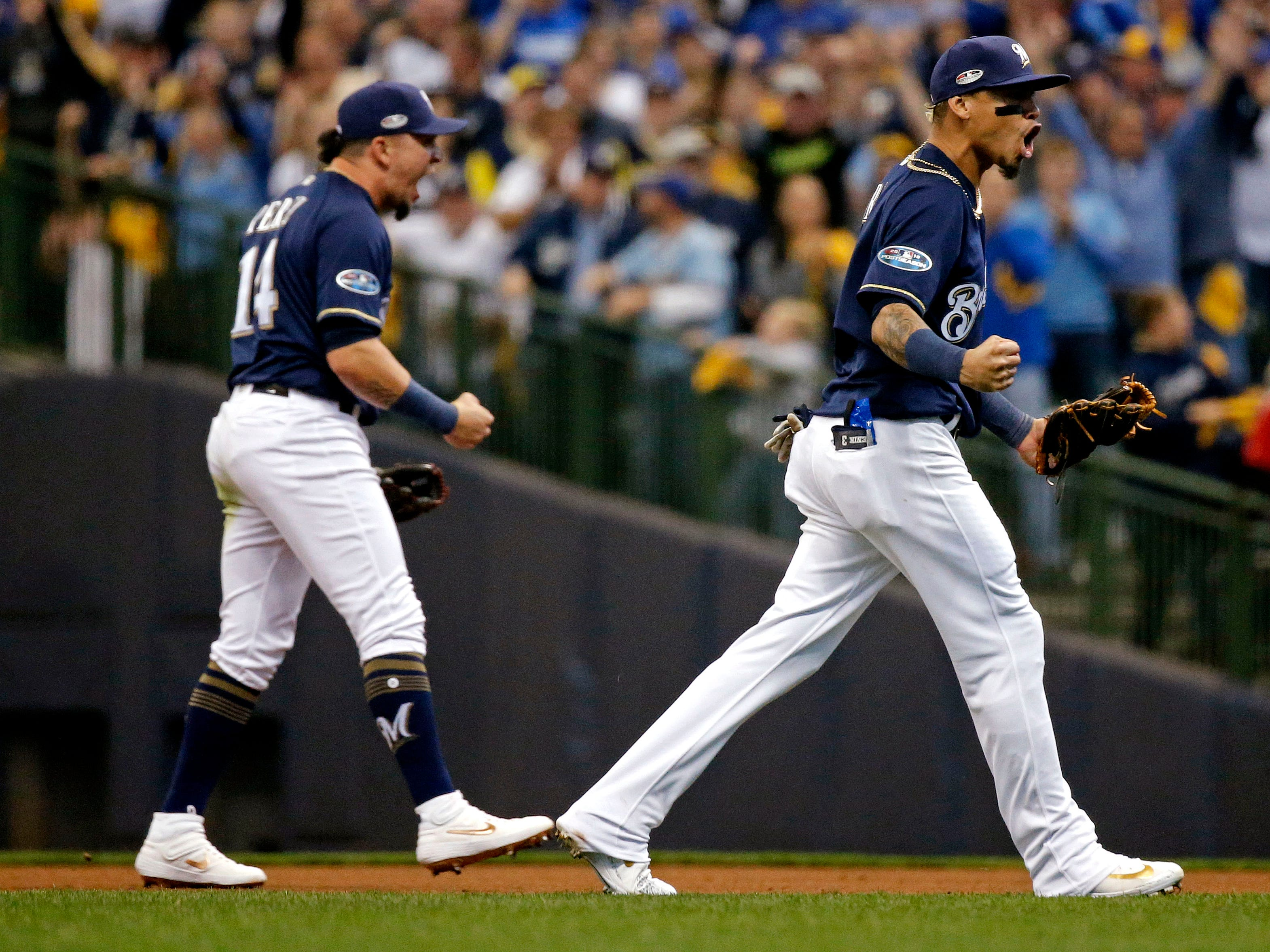 NLCS Game 2: Brewers shortstop Orlando Arcia and second baseman Hernan Perez complete an inning-ending double play in the seventh inning.