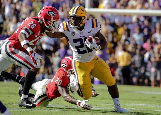 LSU running back Clyde Edwards-Helaire breaks away from Georgia  defensive back Tyrique McGhee (26) and defensive back J.R. Reed during the second quarter at Tiger Stadium.