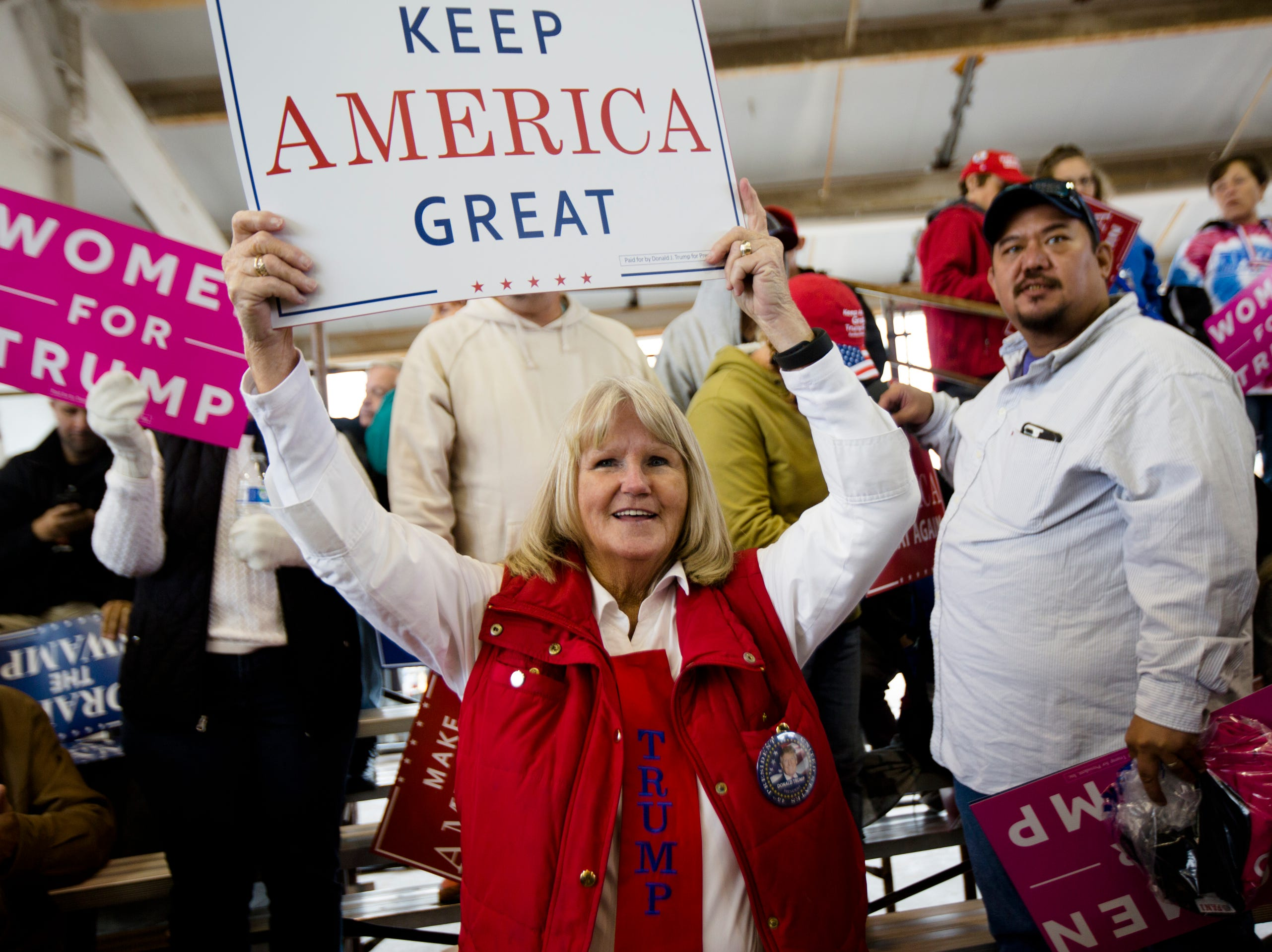 Carol Blasingame, of Cincinnati, waives a sign while waiting for the President at during the Make America Great Again Rally, Friday.
