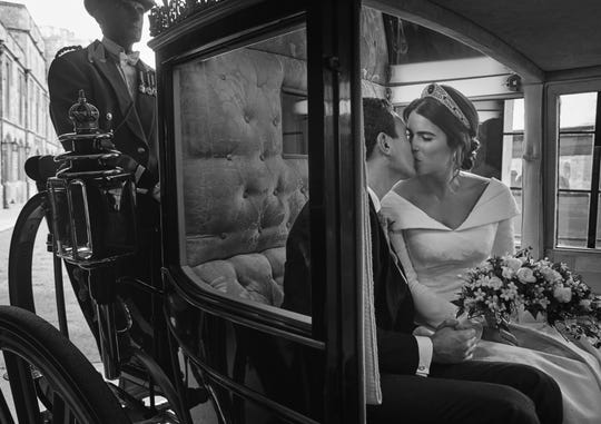 In this photo released on Saturday, Oct. 13 2018 by Buckingham Palace, Britain's Princess Eugenie of York and  Jack Brooksbank embrace, in the Scottish State Coach, upon its return to Windsor Castle following the Carriage Procession after their Wedding, at St George's Chapel on Friday, Oct. 12, 2018.