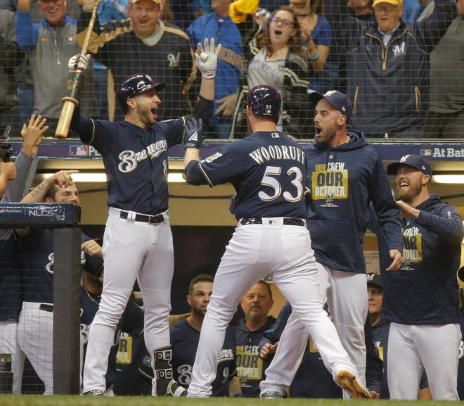 Brewers relief pitcher Brandon Woodruff celebrates with left fielder Ryan Braun (left) after hitting a solo home run during the third inning of NLCS Game 1 at Miller Park.