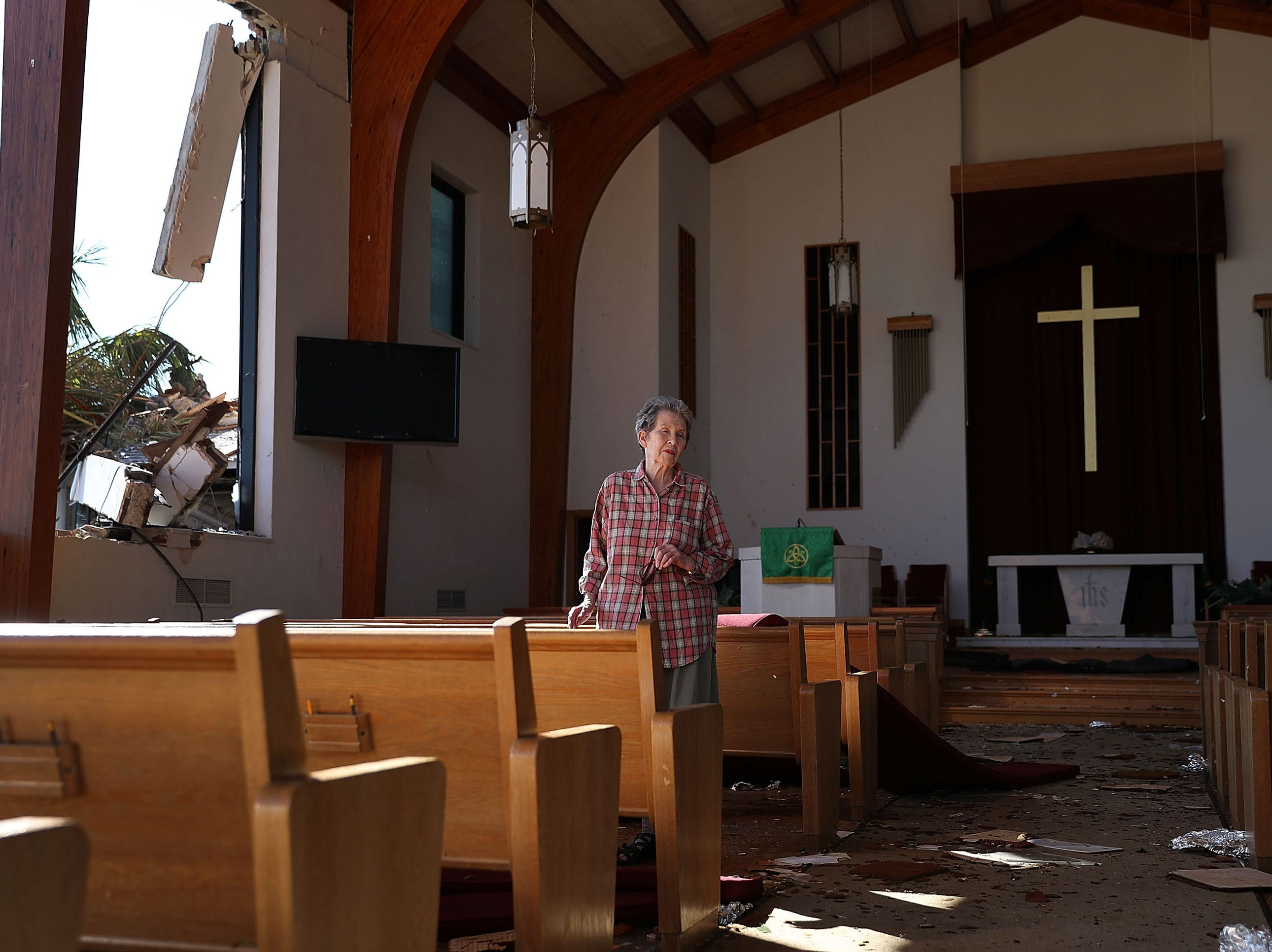 Cynthia Biegler, 81, stands in the church that she has attended since 1962, after two of the exterior walls were blown down when Hurricane Michael passed through the area, Oct. 13, 2018 in Panama City, Fl. The hurricane hit the Florida Panhandle as a category 4 storm causing massive damage and claimed the lives of 17 people.