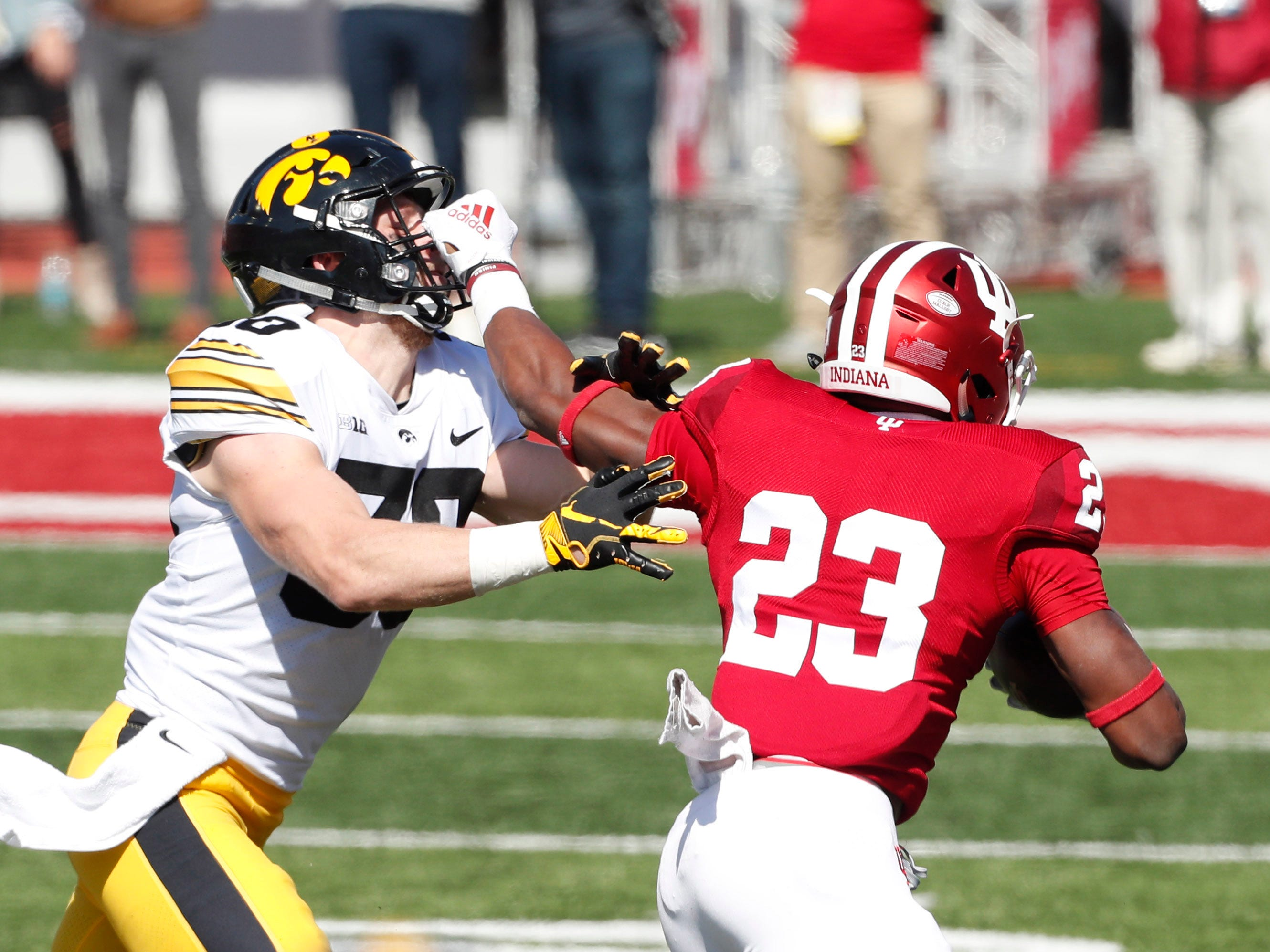 Indiana running back Ronnie Walker Jr. wards off Iowa defensive back Jake Gervase with a stiff arm (and a little bit of face mask).