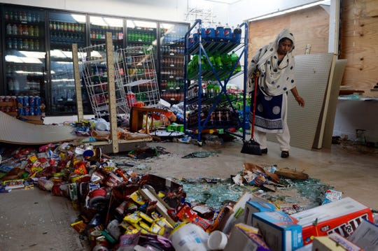 Khodaza Khatun Popi works to clean spoiled food, broken glass and water from the floor of the Shop N Go Jr. convenience store two days after Hurricane Michael blew through Panama City.