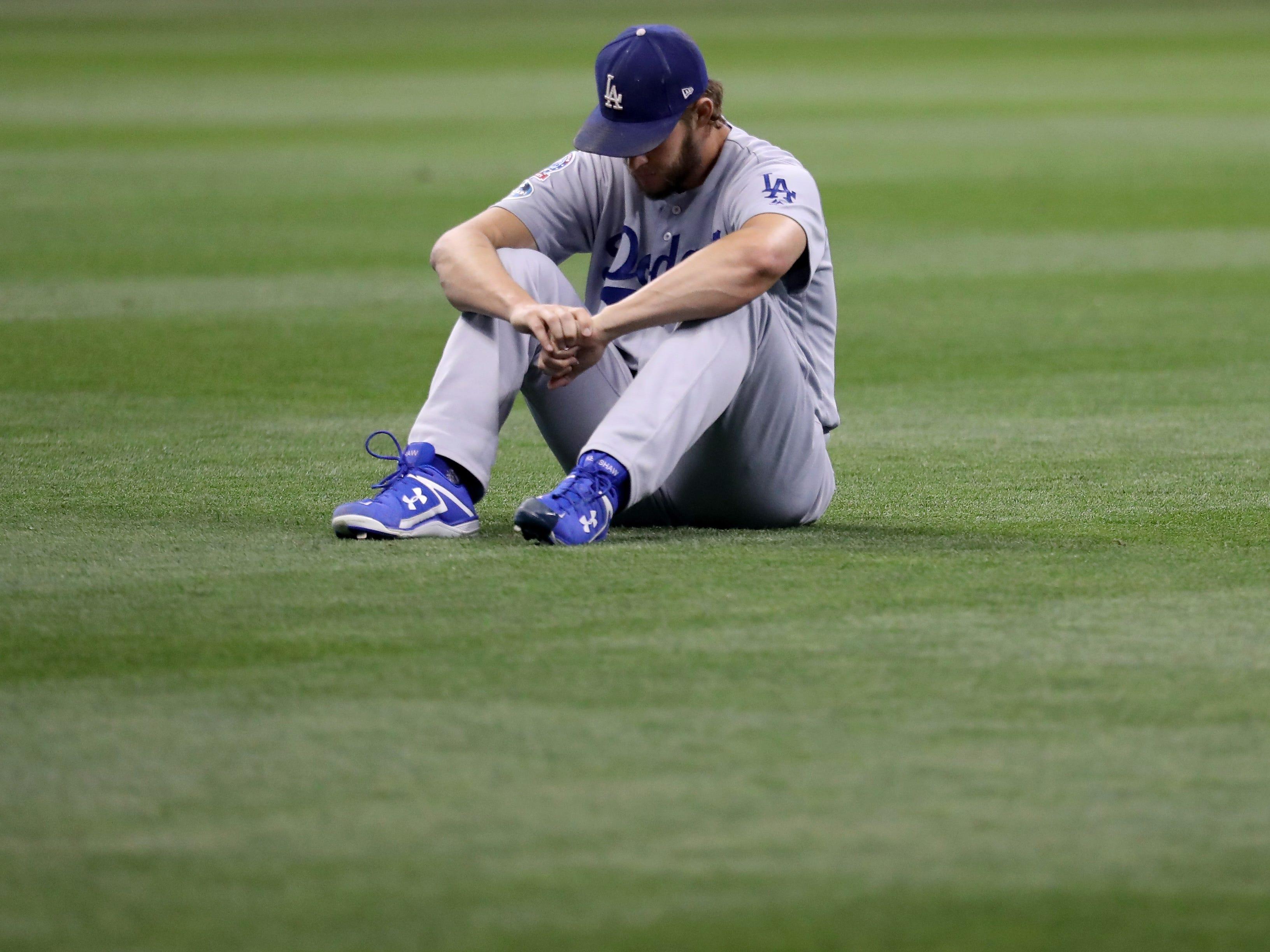 NLCS Game 1: Dodgers' starting pitcher Clayton Kershaw warms up in the outfield.