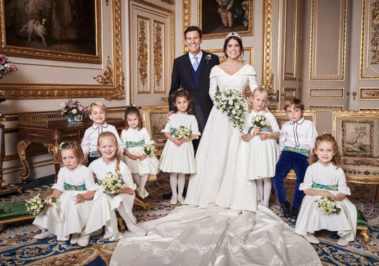 In this photo released on Saturday, Oct. 13 2018 by Buckingham Palace, Britain's Princess Eugenie of York and  Jack Brooksbank are photographed in the White Drawing Room, Windsor Castle with from left, back row, Prince George, Princess Charlotte, Theodora Williams, Isla Phillips, Louis De Givenchy. Front row, Mia Tindall Savannah Phillips and Maud Windsor, following their Wedding, at St George's Chapel, Windsor Castle on Friday, Oct. 12, 2018.