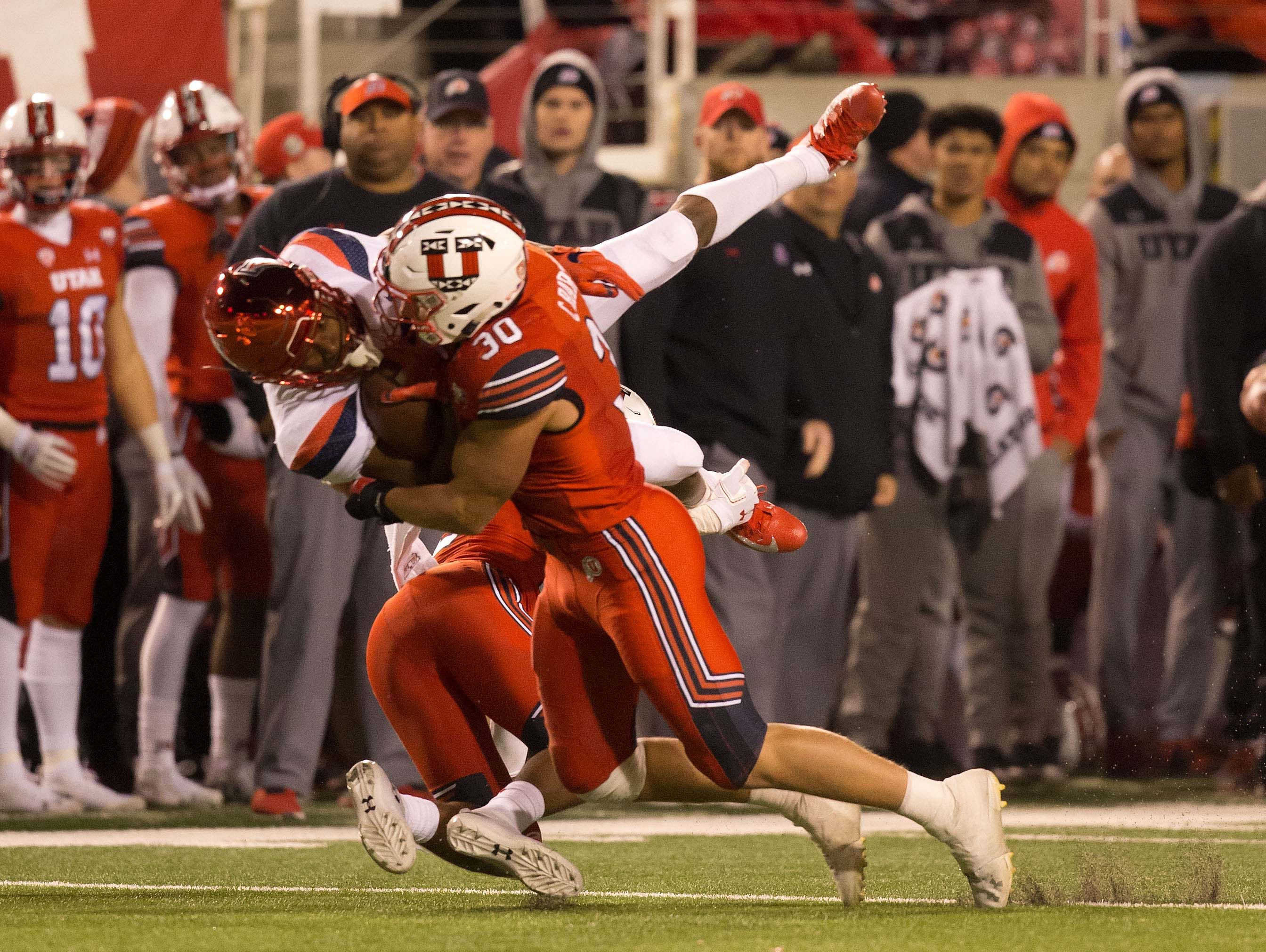 Arizona Wildcats wide receiver Devaughn Cooper (7) is tackled by Utah Utes defensive back Terrell Burgess (26) and linebacker Cody Barton (30) during the second half at Rice-Eccles Stadium.