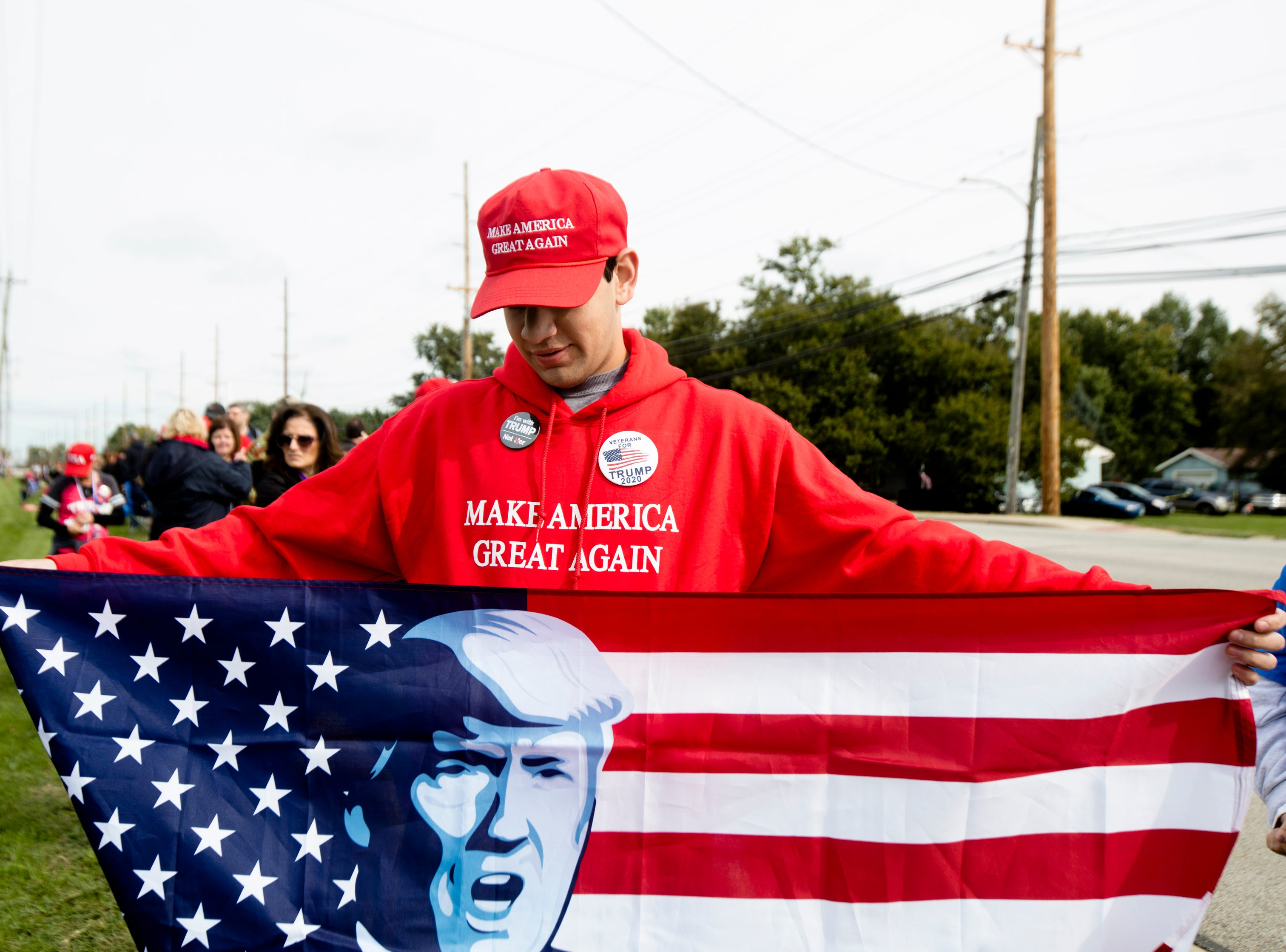 Lorenzo Esquivel holds a a flag while waiting in line for President Donald J. Trump's Make America Great Again Rally.