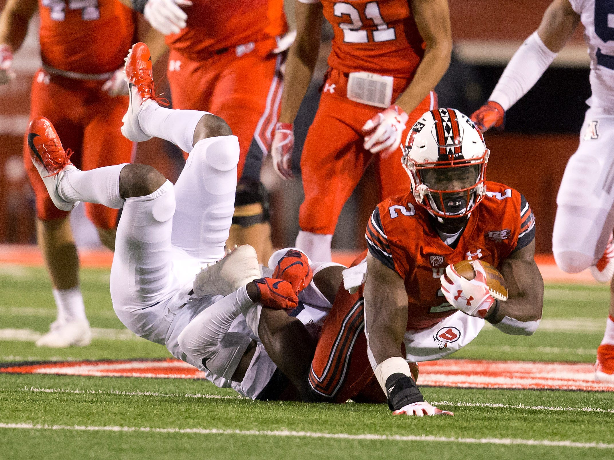 Utah Utes running back Zack Moss (2) is tackled by Arizona Wildcats safety Demetrius Flannigan-Fowles (6) during the first half at Rice-Eccles Stadium.