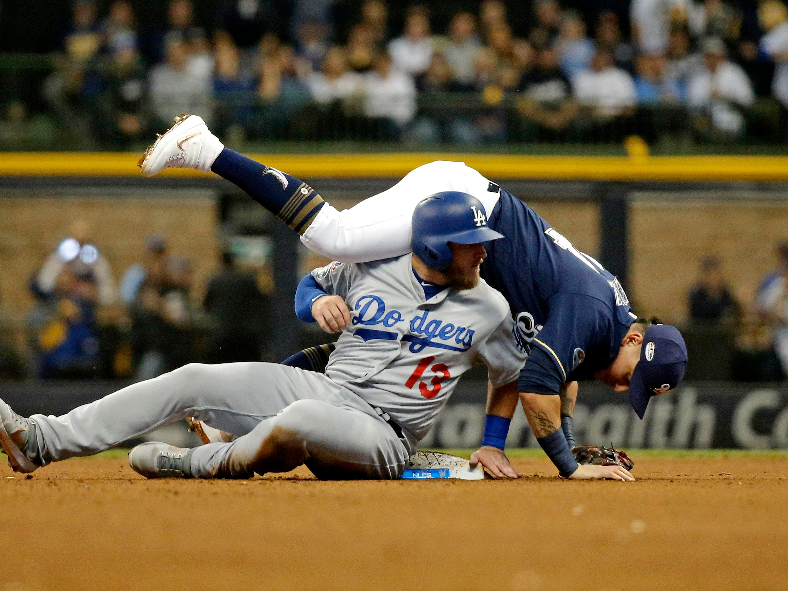 NLCS Game 2: Dodgers' Max Muncy slides through second baseman Hernan Perez during a double play in the eighth inning.