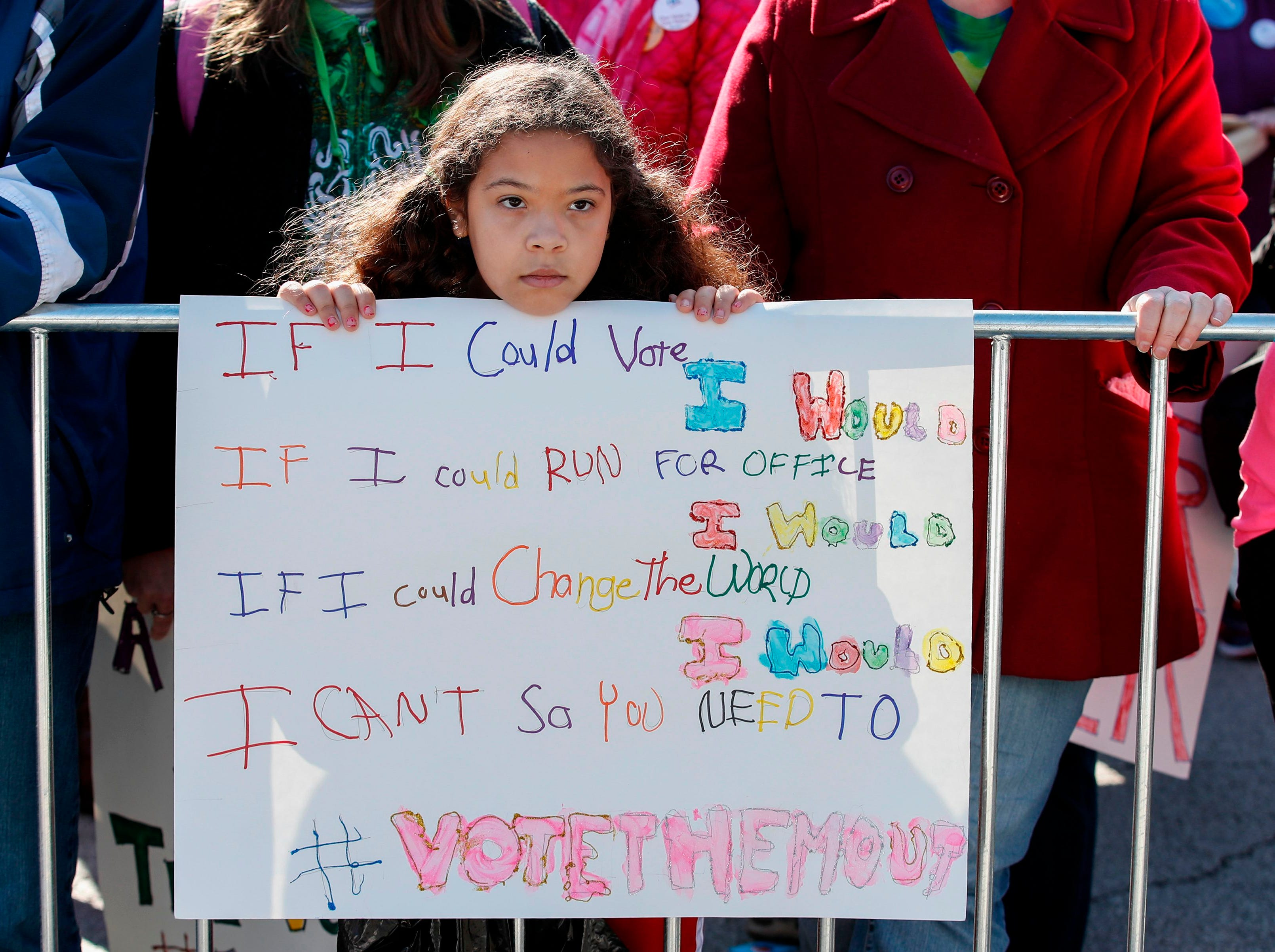 "A young girl listens as women gather for a rally and march at Grant Park on Oct. 13, 2018 in Chicago, Ill. to inspire voter turnout ahead of midterm polls in the United States. Women angered by the bitter fight over a US Supreme Court nominee and what they called the ""anti-woman agenda"" of the Trump administration headed into the streets of Chicago on Saturday in a display of political might. The rally, organized by Women's March Chicago, was designed to spotlight the power and determination of women voters ahead of the crucial November 6 midterm elections, which will determine control of the US Congress. The elections are also being seen as a barometer of President Donald Trump's popularity."