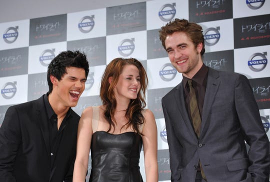 "Robert Pattinson, Kristen Stewart and Taylor Lautner react as they greet fans during a 2009 event to promote ""Twilight"" in Tokyo."