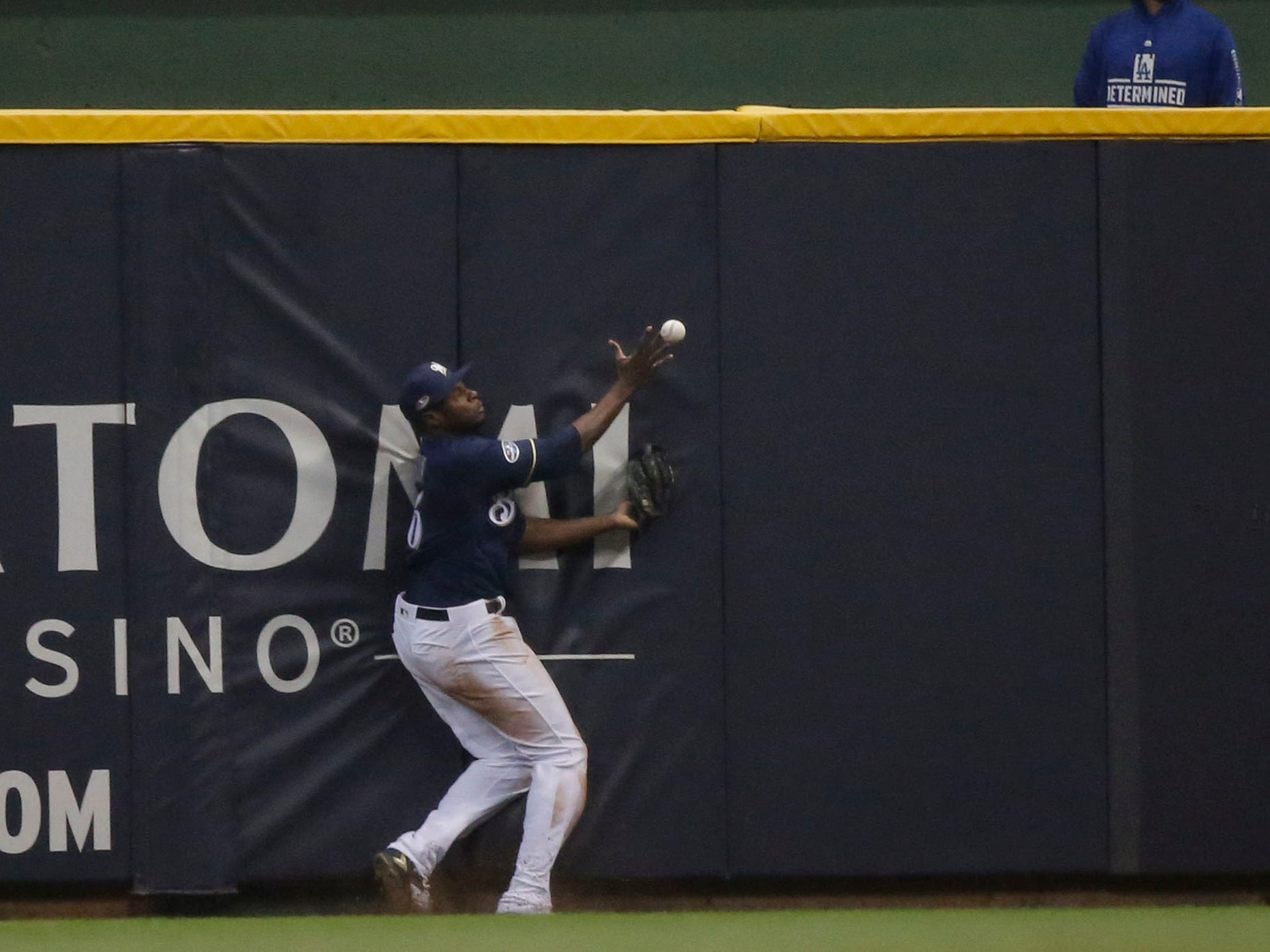 NLCS Game 1: Brewers center fielder Lorenzo Cain fails to catch a fly ball at the wall in the ninth inning.