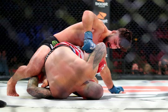 Dennis Buzukja, top, attacks Ryan Castro during a mixed martial arts bout at Bellator 208, in Uniondale, NY on Saturday, Oct. 13, 2018. Buzukja won by 1st round TKO. (AP Photo/Gregory Payan)