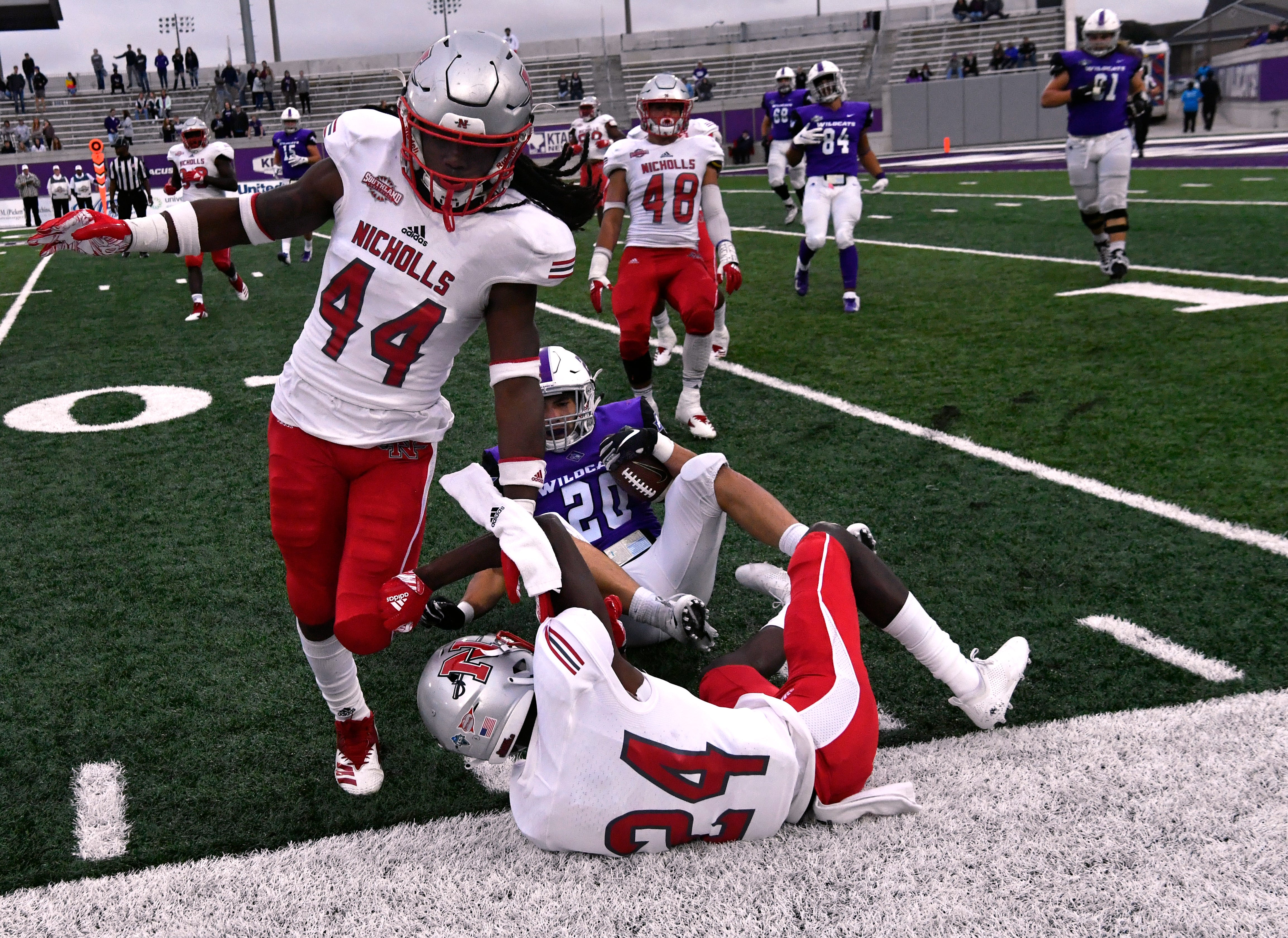 Nicholls University defensive players Ahmani Martin (left) and Darren Evans tumble out of bounds after tackling Wildcats running back Billy McCrary in the final minutes of Saturday's game Oct. 13, 2018. Final score was 28-12, ACU.