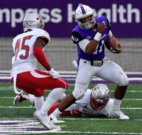 Nicholls defensive back Corey Abraham falls to the ground as ACU running back Tracy James faces off against defensive back Austin Dickerson during a Southland Conference game. ACU won the game 28-12 on Oct. 13 at Wildcat Stadium.